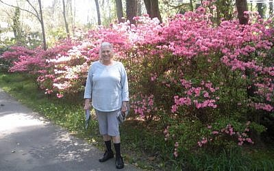 Judy in front of blooming flowers at their previous home.