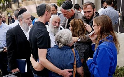 Rabbi Yisroel Goldstein, center, surrounded by his congregants on Sunday outside the Chabad of Poway in Poway, Calif. He was shot in an attack at the synagogue on Saturday, the latest to shake leaders of houses of worship.// Sandy Huffaker/Agence France-Presse — Getty Images