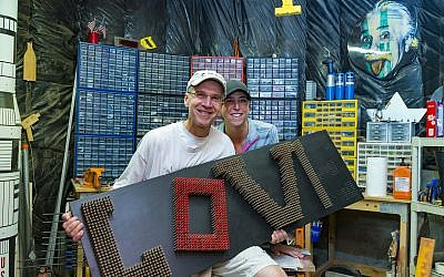 "Photos by Duane Stork // Scott Shulman poses with physician wife Rhonda Taubin in his workshop to display ""LOVE,"" composed of 1,830 deck screws. Note the ""E"" is in progress. Shulman does not sell his work, which goes to decorate his medical offices or local charities."