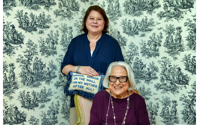 "Photos by Duane Stork // Julie and Jean share the joy of Mother's Day with the pillow that reads, ""Mirror, mirror on the wall, I am my mother after all."" Jean needlepointed the pillow."