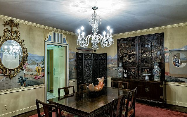 Jean's dining room has the black Waterford chandelier, a carp soup terrine, and the wallpaper brought over from the Sussex home.