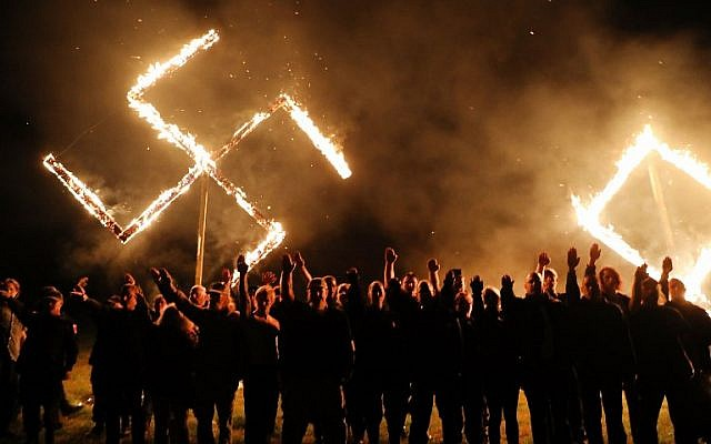 Spencer Platt/Getty Images/AFP // Members of the National Socialist Movement, one of the largest neo-Nazi groups in the U.S., hold a swastika burning after a rally on April 21, 2018, in Draketown, Ga.