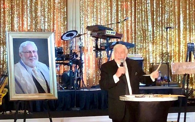 Photo by Bernice Isaac // Man of the hour, Rabbi Lewis takes center stage. Behind him are his portrait and a plaque announcing a new rabbinic suite in his honor.