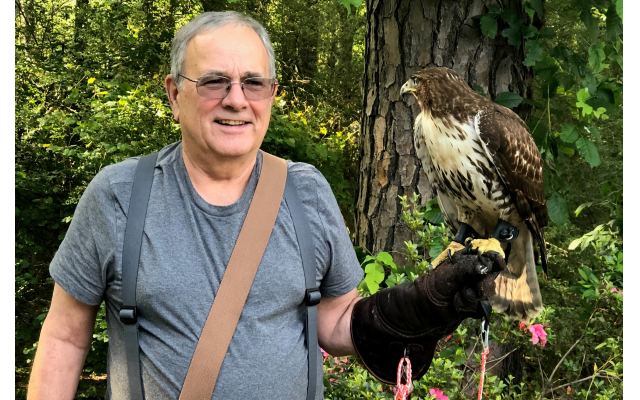 Greg Ames uses a thick glove on which to perch his red-tailed hawk, whom he has trained to kill prey.