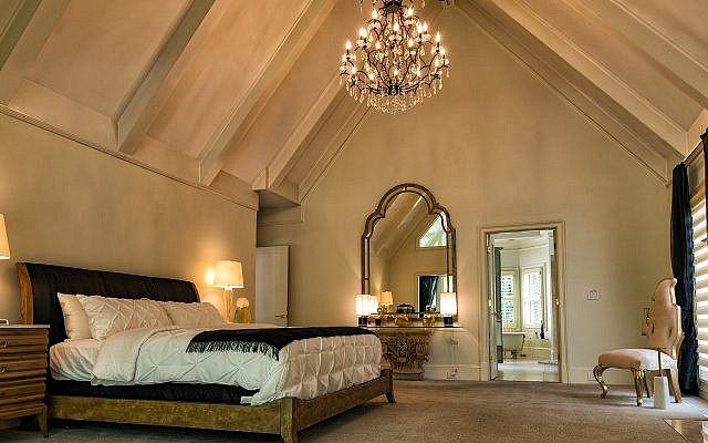 The majestic master bedroom has end tables by Kreiss. The silhouette chair on the right is by Christopher Guy. The far wall houses the perfume Factice collection.  Chandelier is Savoy House Lighting.
