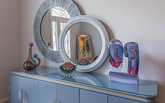"The Larrabees refinished this blue console from Habif's original buffet. The glass sculpture on the right is Murano glass from Venice, ""Picasso's Lovers"" by Dino Rosin."