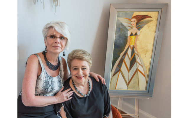 "On left, designer Julia Larrabee poses alongside Sherry Habif, who enjoys her entrance foyer with Alina Eydel's intricately beaded original  ""Only the Art of the Girl in a Dress"""