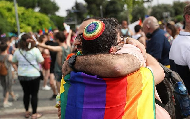 Two people wearing rainbow colors embrace at the parade.
