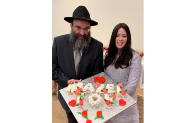 Rabbi and Mrs. Minkowicz hold a dessert display by Jodie Sturgeon of For All Occasions and More catering.