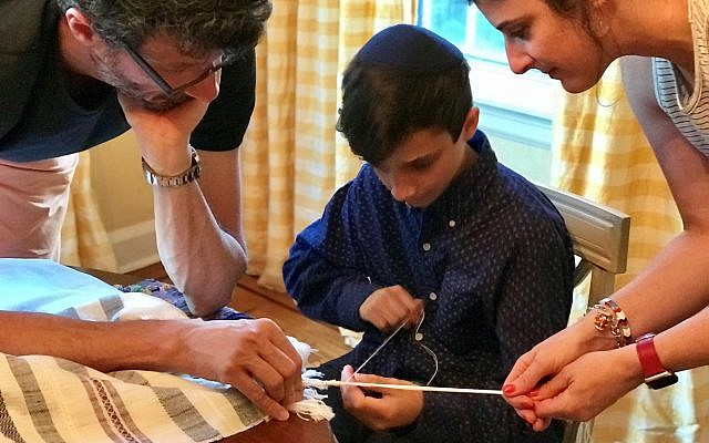 With help from his parents, Gioel (left) and Ronni, Luca Molinari ties the final knots days before his bar mitzvah.