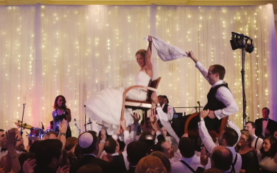 Bride and groom holding a custom-made The Wedding Dance Napkin during the horah.