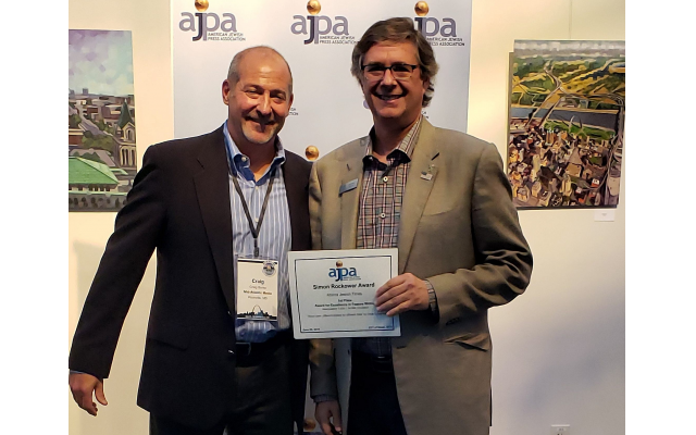 AJT Publisher Michael Morris, right, receives one of the paper's four AJPA Simon Rockower Awards from Craig Burke of Mid-Atlantic Media.
