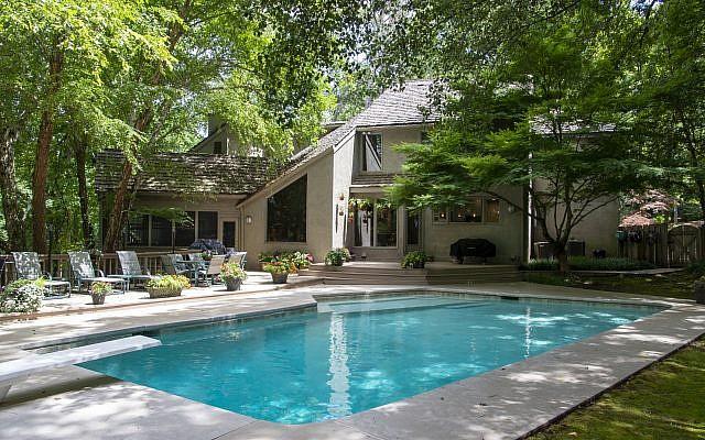 The geometric pool shape replicates the angles of the house frame.