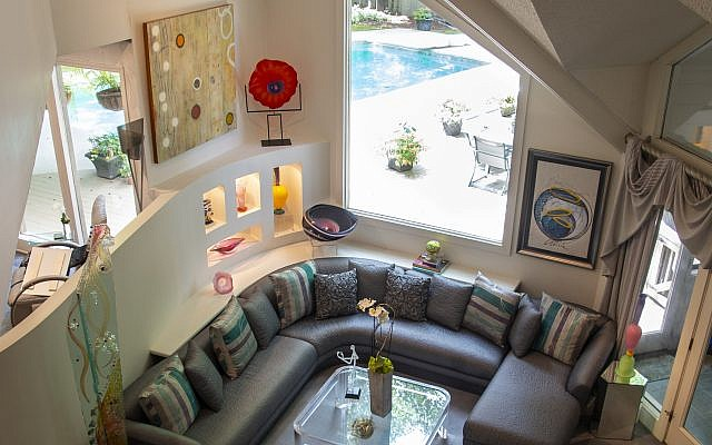 """Aerial view of living room: The Wands reconstructed their main level space to add curved walls that better showcase art. The tall glass spire on left (Vespermann Gallery) is """"Queen Column"""" by Susan Pelish and family.  The asymmetrical bowl is David Goldhagen. Dale Chihuly's """"Basket"""" lithograph is far right. Bressler is noted for her exceptional eye for color."""
