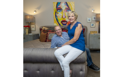 "Photos by Heidi Morton // Linda and Ron Wand ""chill"" in the master bedroom under the oil they acquired in Playa del Carmen. Pillow fabrics are from the Jim Thompson house in Bangkok."