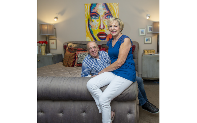 """Photos by Heidi Morton // Linda and Ron Wand """"chill"""" in the master bedroom under the oil they acquired in Playa del Carmen. Pillow fabrics are from the Jim Thompson house in Bangkok."""