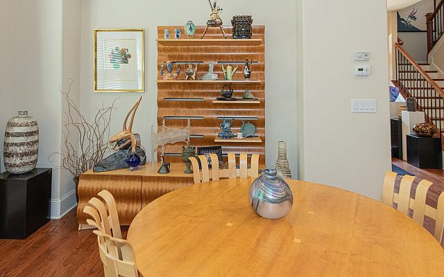 "The American maple kitchen table is surrounded by chairs by Frank Gehry facing a variety of teapots and sculpture. Weinberg-Benson did the tall pot on the left. Reed Minty's ""Dream Interpretation"" is adjacent to the frosted glass piece by Ginny Ruffner."