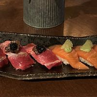 """Over the top"" taste on this dish: Blue fin tuna topped with black truffles and caviar, left, and wasabi salmon with citrus and green tea salt, right."