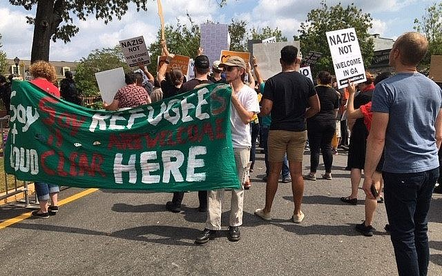 "Counter-protesters held up signs with phrases such as, ""Say it loud, say it clear, refugees are welcome here."""