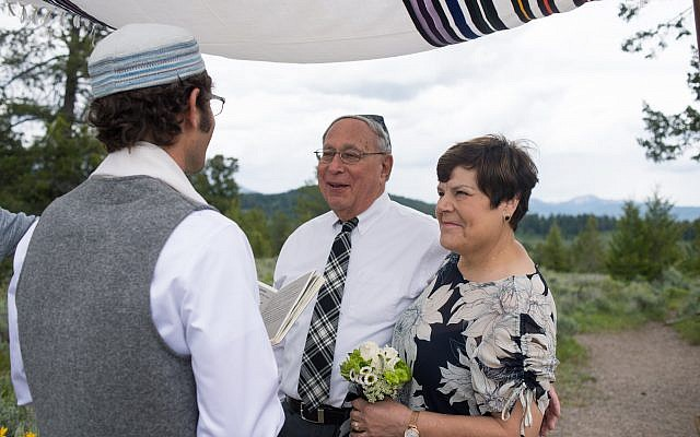 Photo of Gerry and June Neumark renewing their vows under son Jay's tallit.