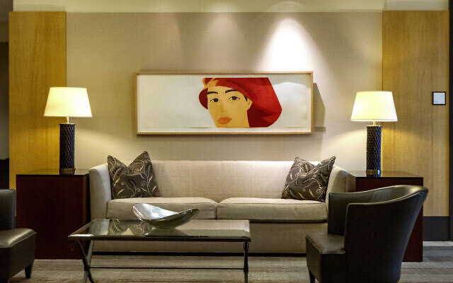 "This stunning Alex Katz ""Red Cap"" 1990 etching oversees a couch setting in the adjoining lobby."