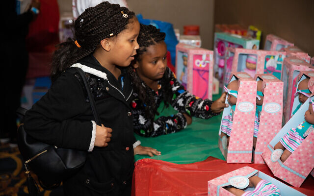 Making their way through the room, two younger partygoers stop to examine a doll.