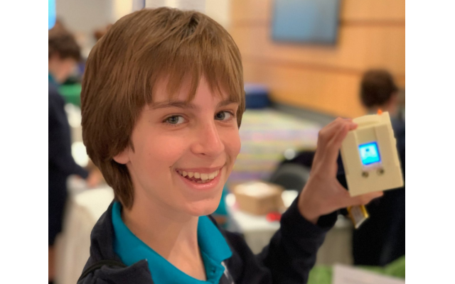 Micah Kopelman proudly displays the mini Mac computer created with a 3D-printed computer body and coded with Python, a programming language platform.