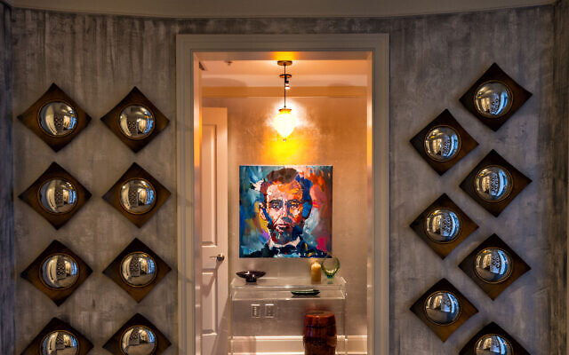 """The Gould foyer displays 30 mirrors found and arranged by Arlene. Above is a hand-blown light fixture from Poland. Center is Penley's """"Abe Lincoln."""""""