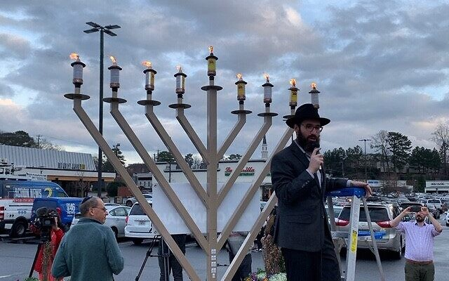 Rabbi Yale New of Chabad of Toco Hills lights the menorah.