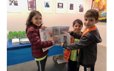 Davis Academy fifth grader Leora Sokol and her brothers pose with the AJT, pointing at her submission.
