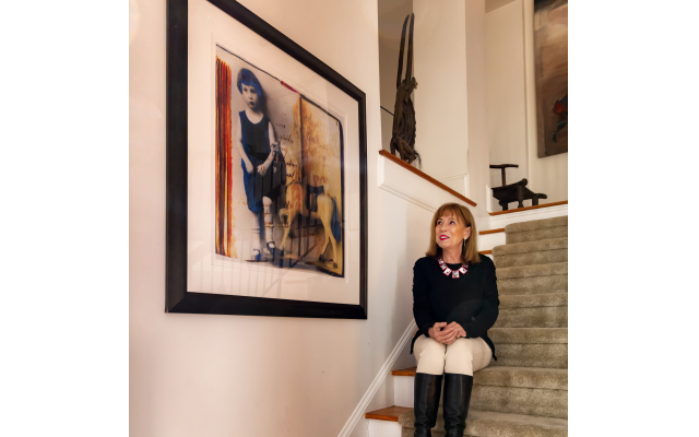 Multifaceted artist Lesley Price relaxes on her staircase wearing a colorful acetate necklace by South African Beverley Price. Beside her is one of the postcards preserved from her father's youth in Germany.