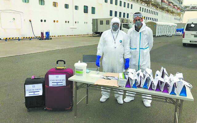Photo via Israeli Embassy Tokyo // Officials wearing protective clothing wait for Israeli passengers to leave the Diamond Princess cruise ship, where they spent two weeks in quarantine.