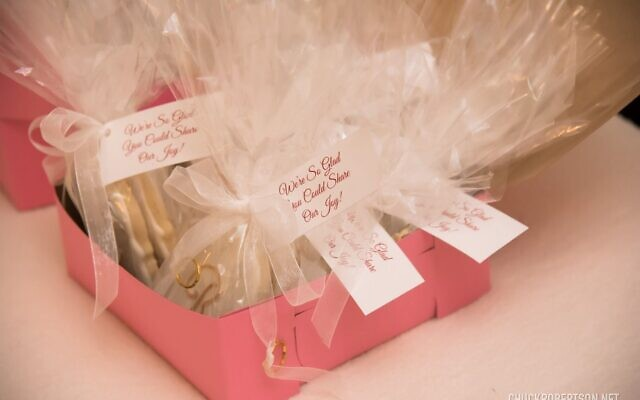 """Andrea's favorite touches were the white iced shortbread cookies with a gold """"R"""" and two wedding bands for guest takeaways."""