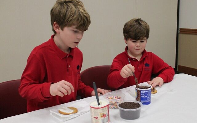 Josh and Noah Friedberg decorate cookies as a community service project.