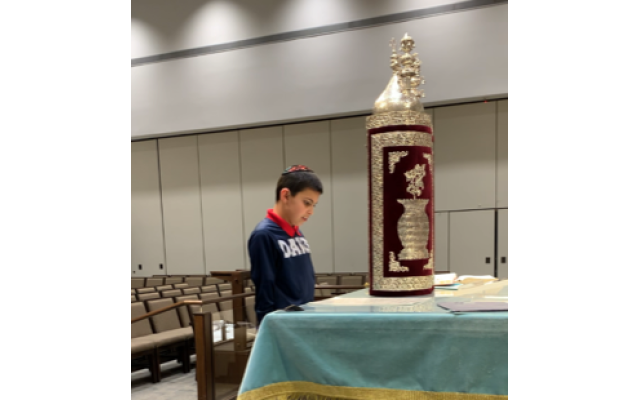 Noah Flome practices his Torah reading from the Sephardic scroll