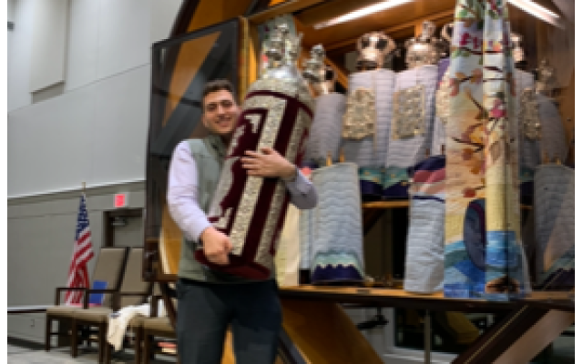 Liam Mass holds the Torah he will read from for a relative's bar mitzvah. He also used the scroll for his bar mitzvah many years ago.