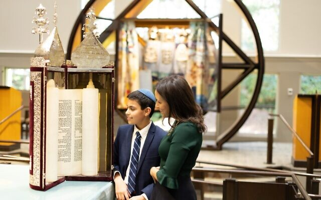 Traci Flome with son Noah admiring the historic family Torah.