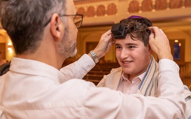 Noah Lipis puts on tefillin for the first time with his cantor.