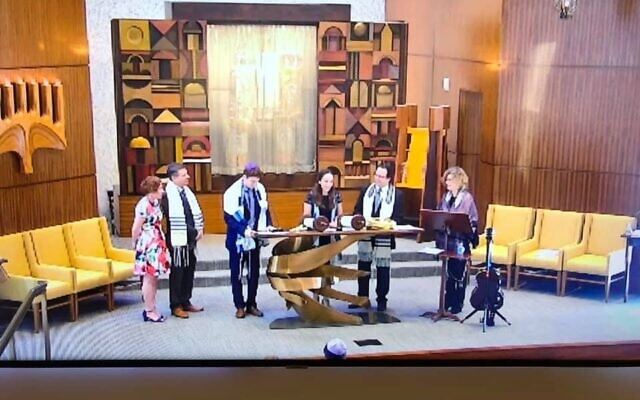 Standing on the bimah at Temple Sinai on March 21 as Abby Simon became a bat mitzvah were Rachel and Matt Simon, parents; Eli Simon, brother; Abby Simon; Rabbi Bradley Levenberg and Cantor Beth Schafer.