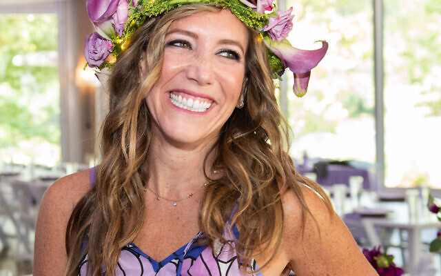 A glowing 40-year-old Samantha wore a garland of purple-toned flowers.