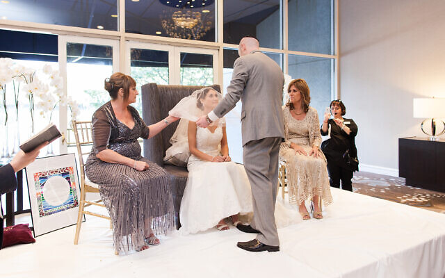 Photo by Gandy Photographers// The groom places the veil on his bride during the bedeken at the Newman-Kaplan wedding.