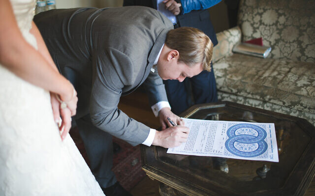 Photo by Victoria Huff Photography// Evan Staley signs his ketubah before his wedding at 550 Trackside in Lawrenceville.