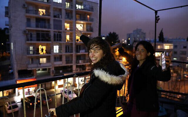 Women in Jerusalem applaud medical staff battling coronavirus, March 19, 2020 (Yossi Zamir/Flash90)