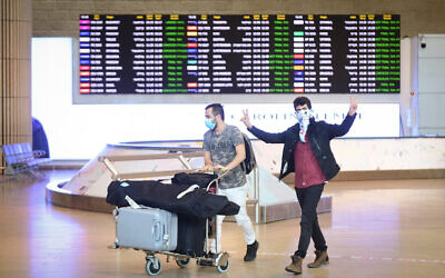 People wear face masks arrive at Ben Gurion International Airport on March 11, 2020. (Flash90)