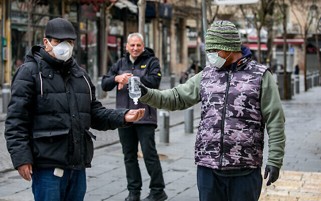 A merchant selling alcogel hand sanitizer to passersby in central Jerusalem on March 18, 2020. (Olivier Fitoussi/FLASH90)