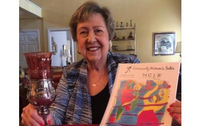 NCJW Atlanta President Sherry Frank displays the haggadah created for the annual Community Women's Seder.