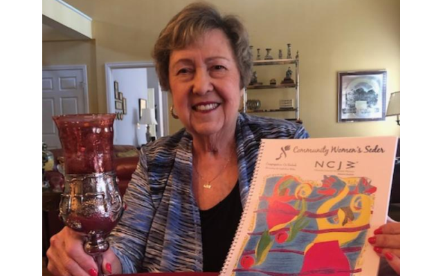 NCJW Atlanta President Sherry Frank displays the haggadah created for the annual Community Women's Seder.