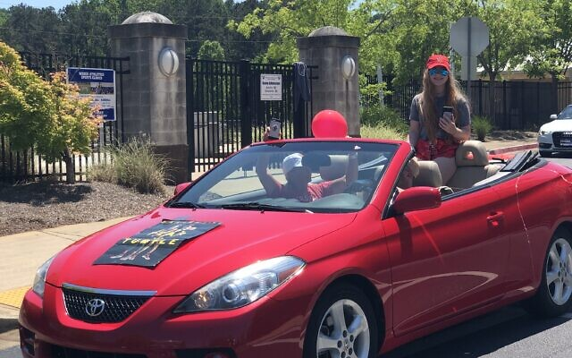 Brooke Orenstein pops out of her red convertible as part of the Weber senior commitment day parade.