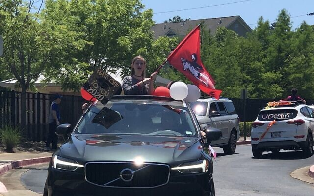 Sadie Levy is all about flag waving during the Weber commitment day parade.