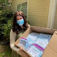 Bracha Slavaticki, the co-director of Chabad Decatur, with a box of masks for community distribution.
